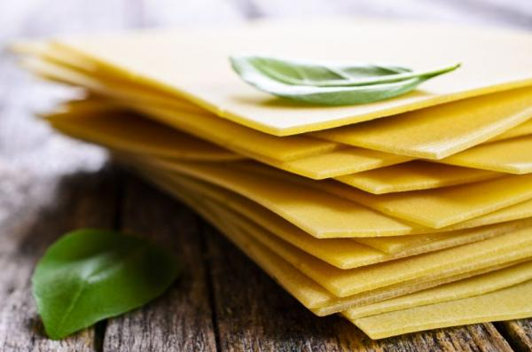 Sheets for lasagna with Basil leaves laid on a wooden surface